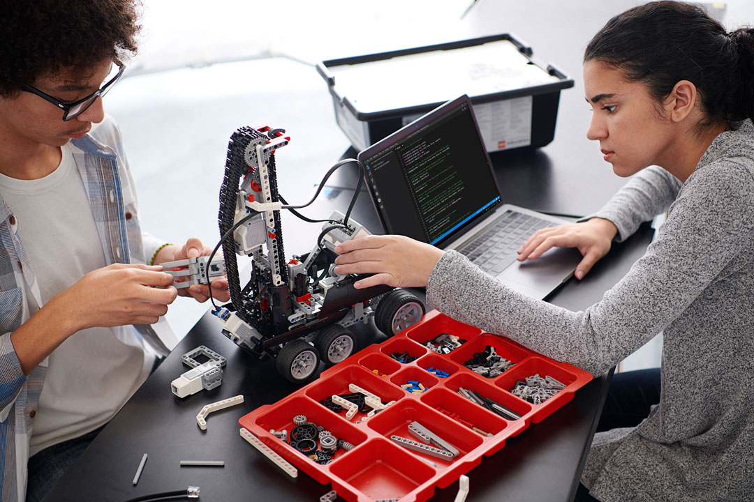 High school boy and girl program their LEGO Education EV3 using Mirco Python.