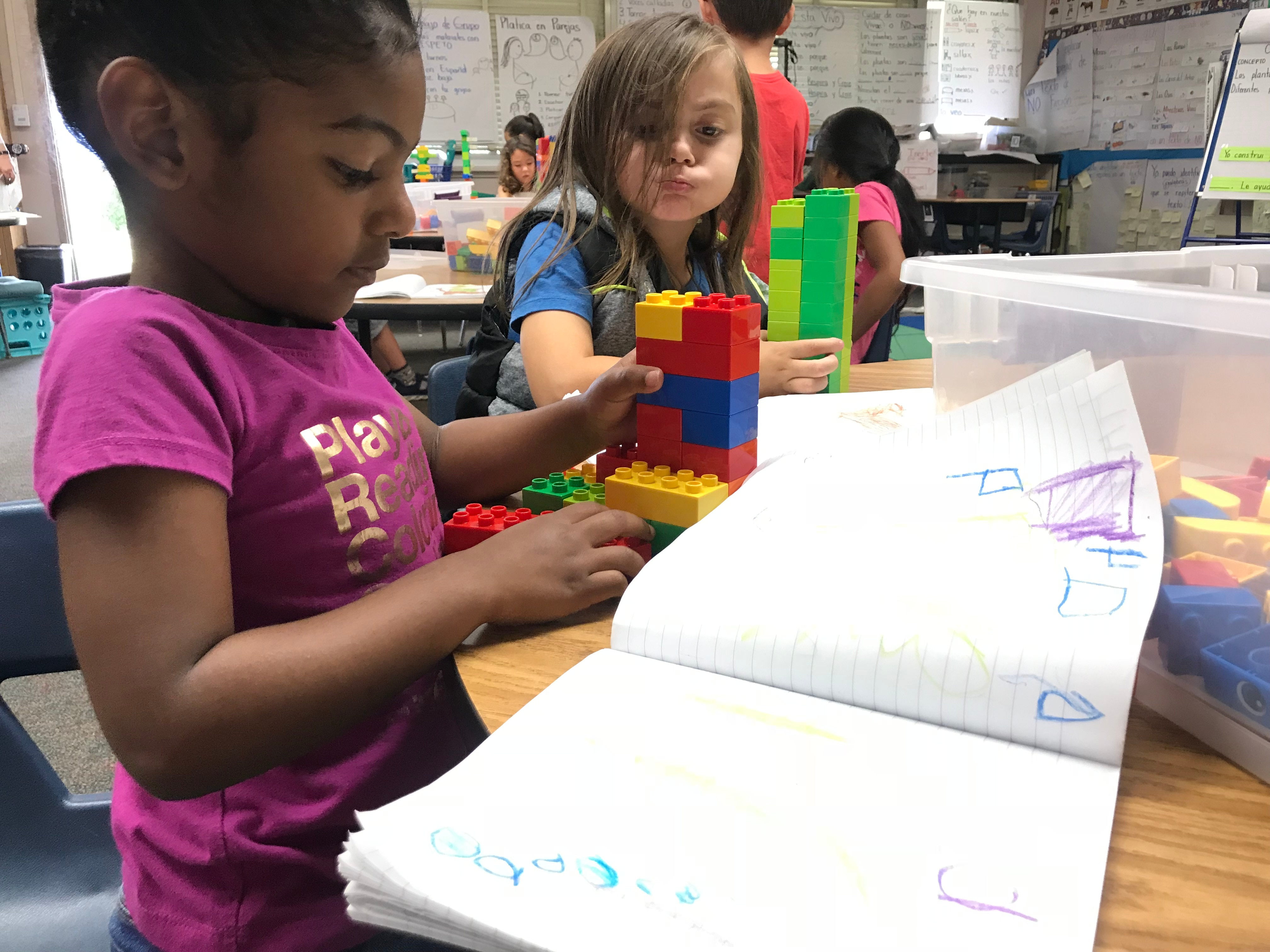 Young girl creating with LEGO Education's products. Another little girl is looking on.