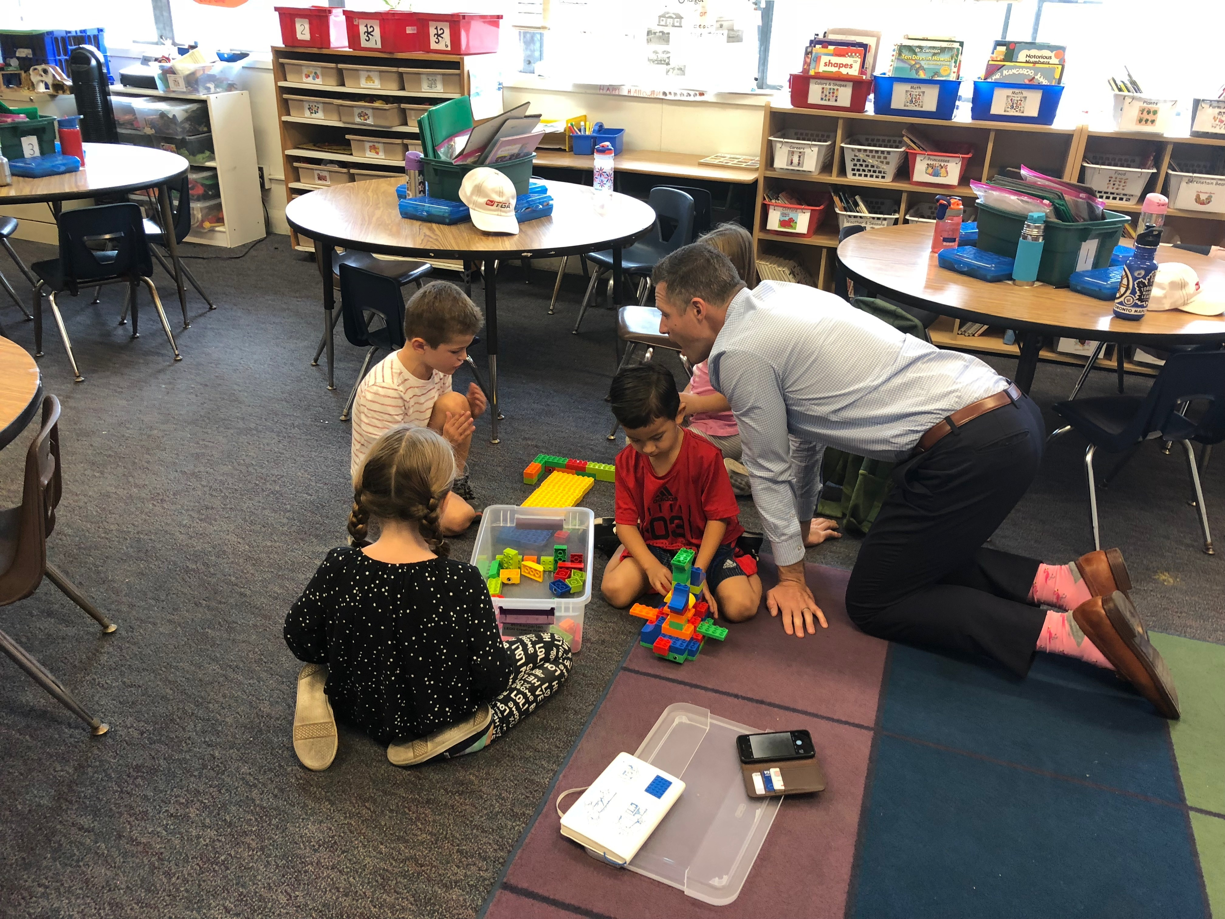 A group of kids on the floor playing with LEGO Education's Early Learning solutions. A teacher is on his hands and knees engaged with the students.