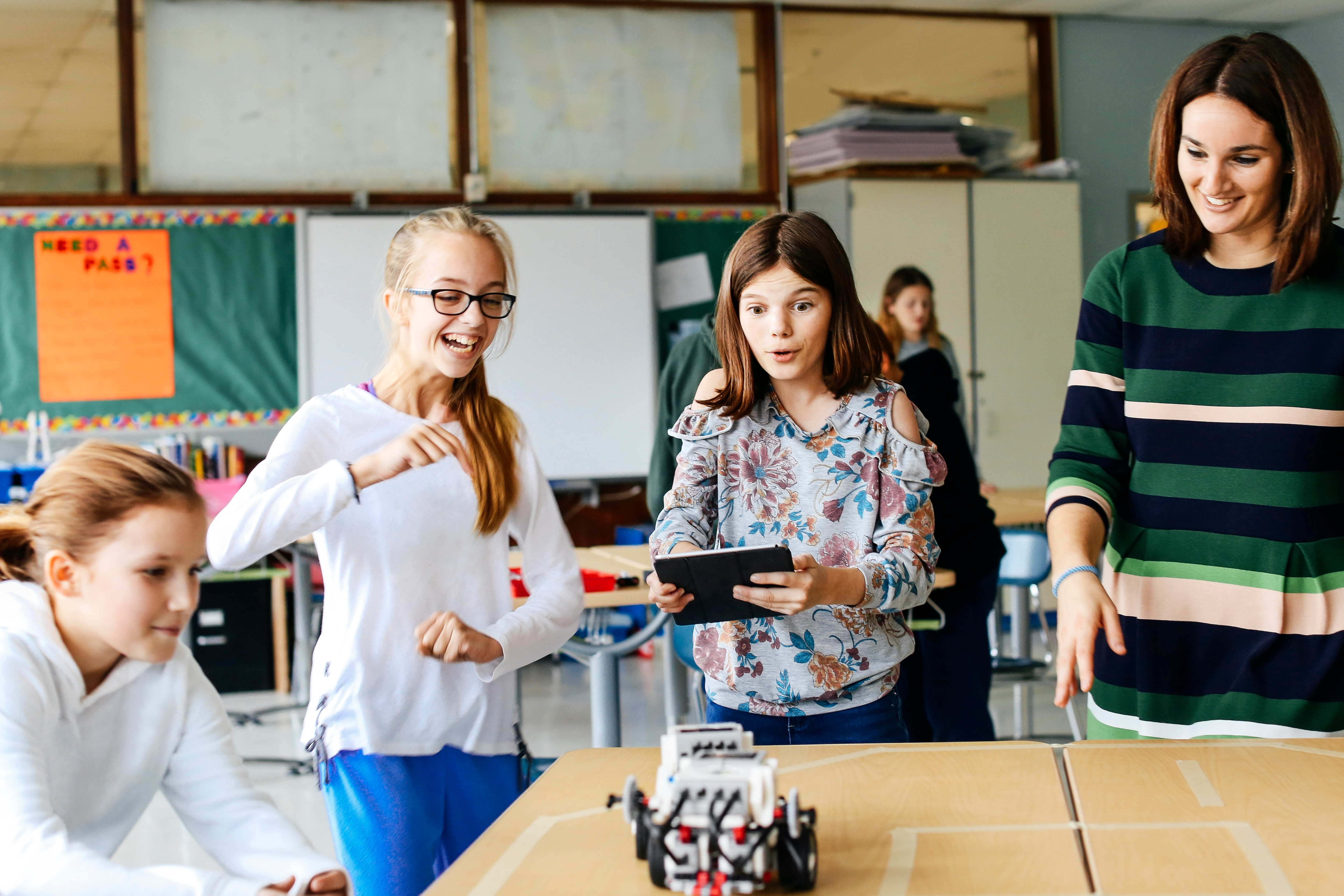 Three students and a teacher programming a LEGO Education MINDSTORMS EV3 robot