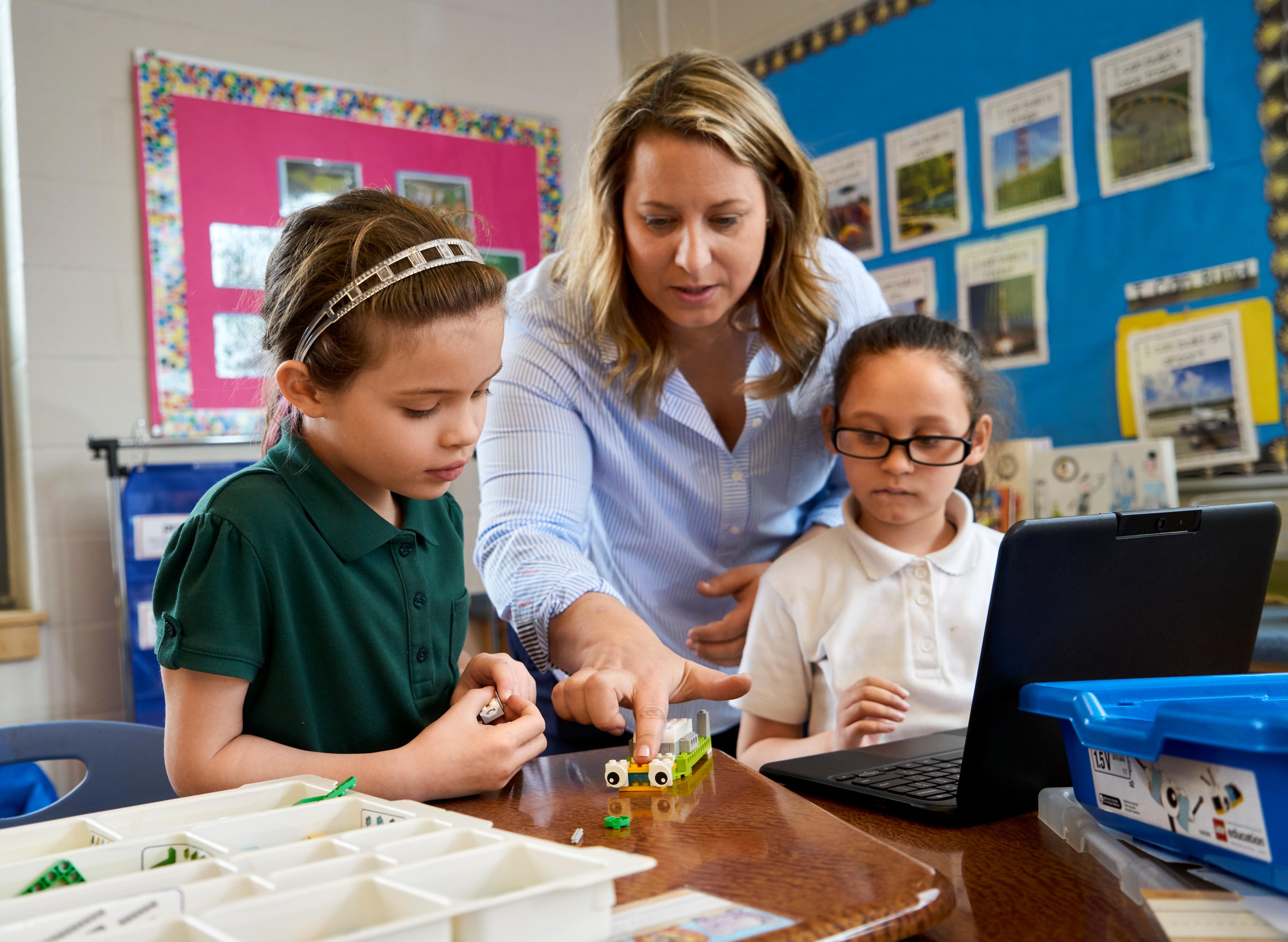 Teacher explaining two primary school girls how LEGO Education WeDo 2.0. works