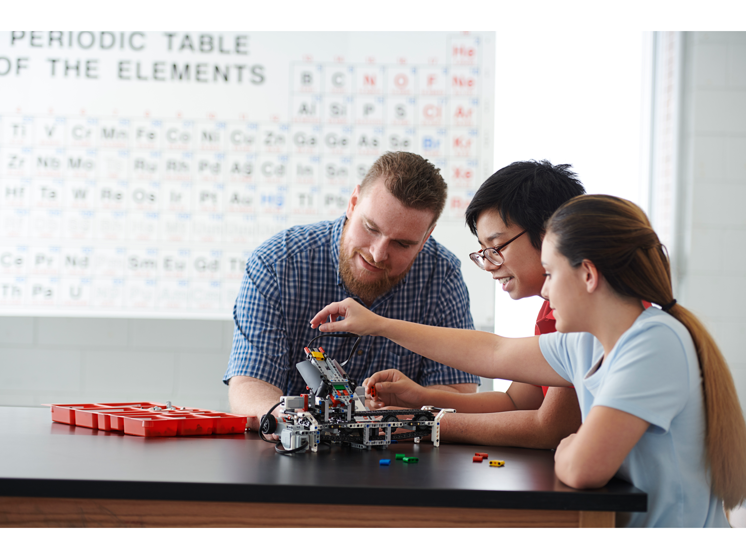 High school teacher instructs two students on how to use LEGO MINDSTORMS Education EV3