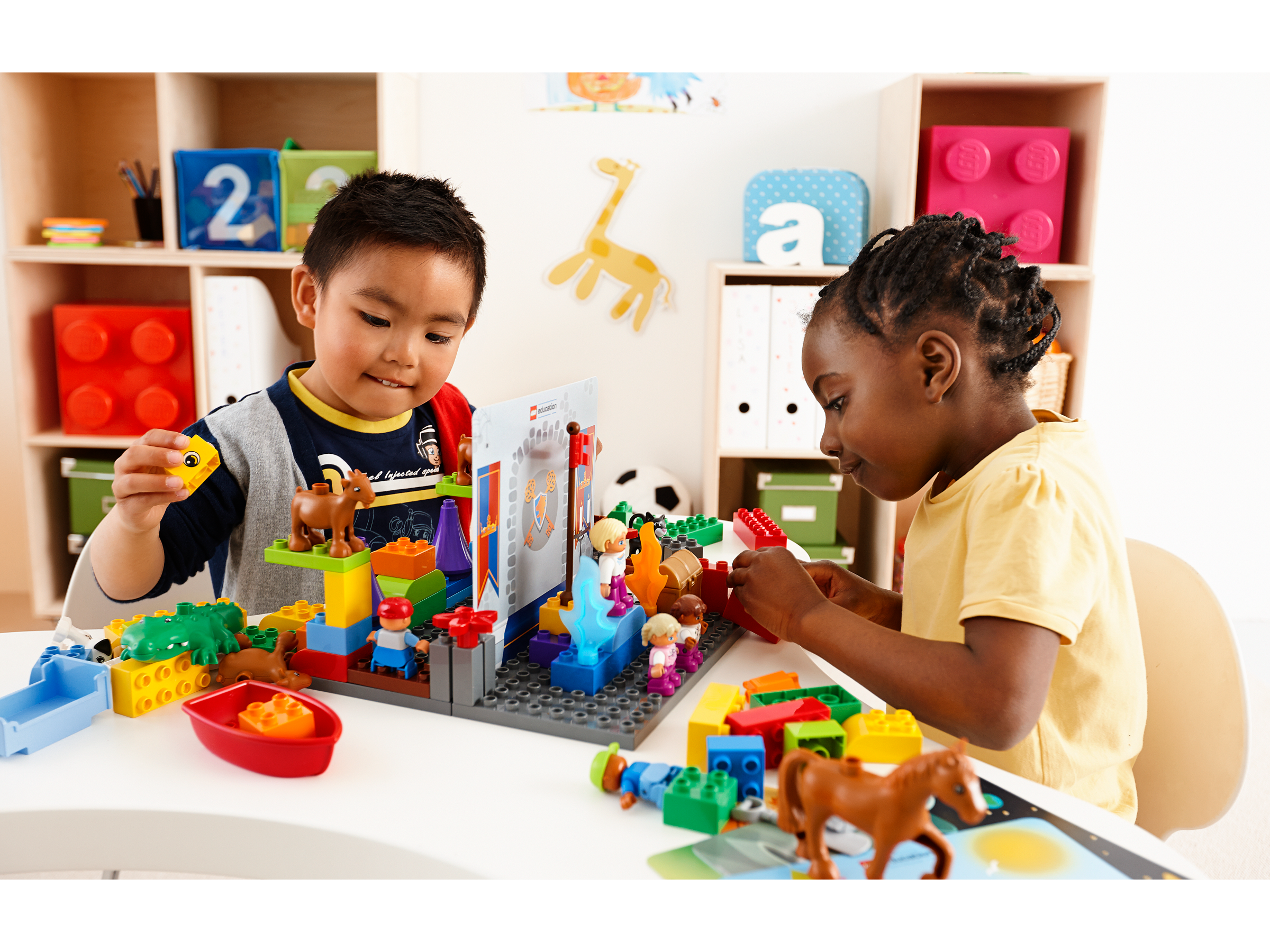 Two preschool children playing with StoryTales by LEGO® Education, developing their storytelling skills.