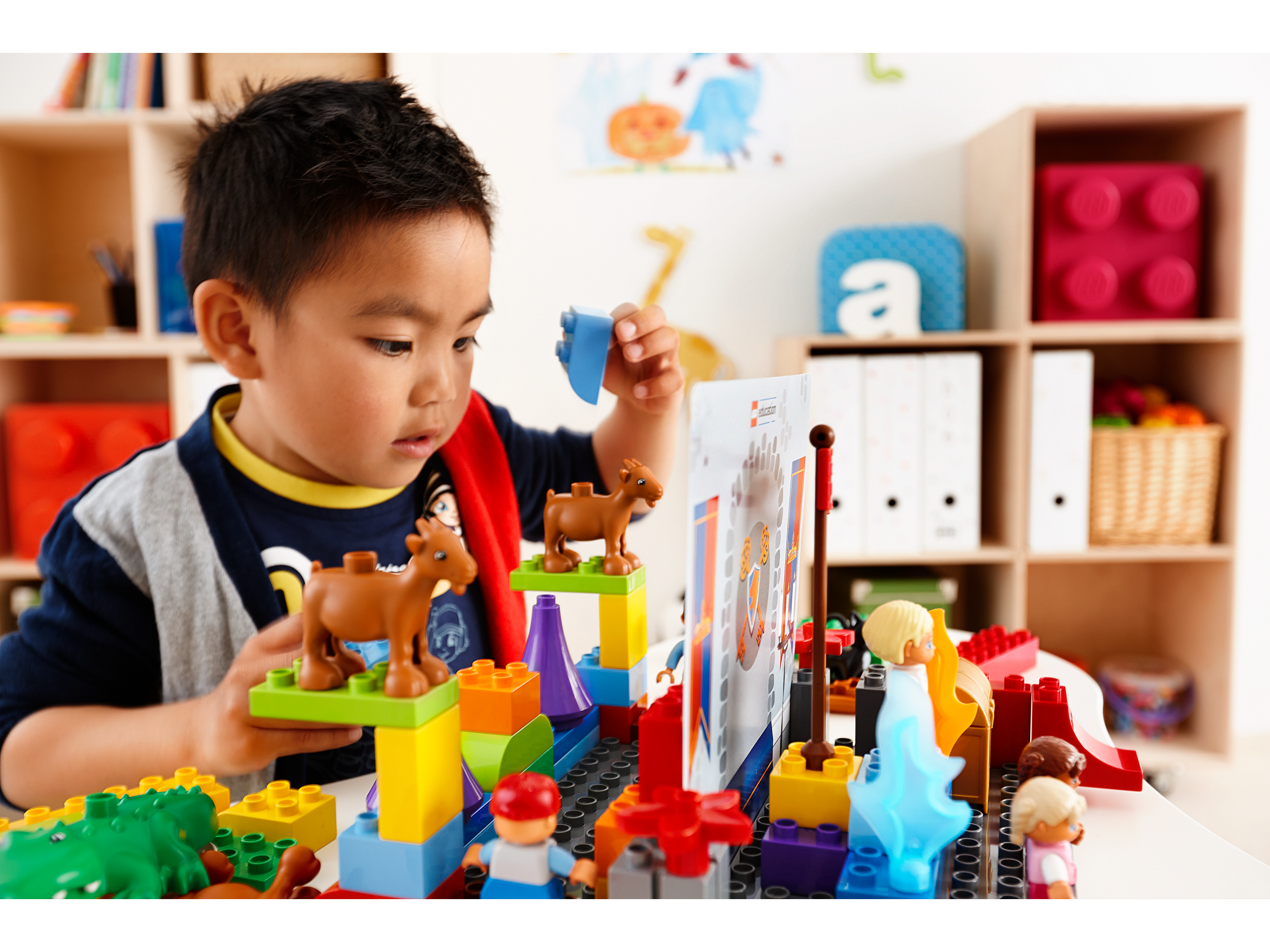 Preschool boy playing with StoryTales by LEGO Education, developing his storytelling skills.