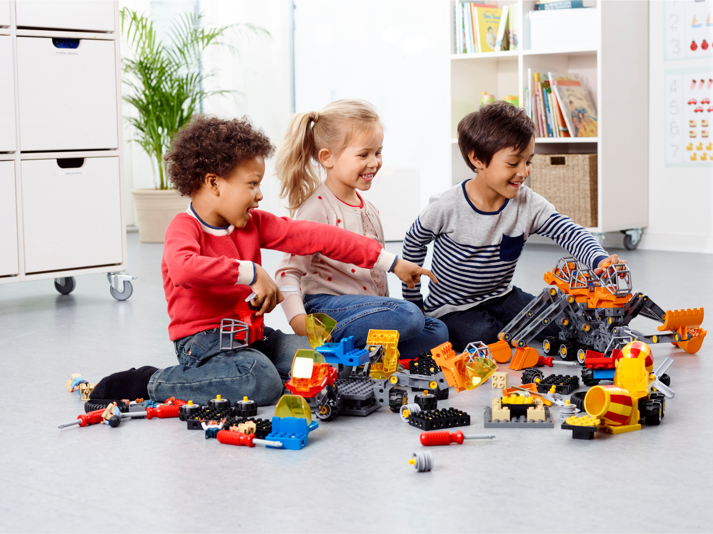 Three preschool children playing with Tech Machines Set with Storage by LEGO® Education, developing their fine motor and problem-solving skills.