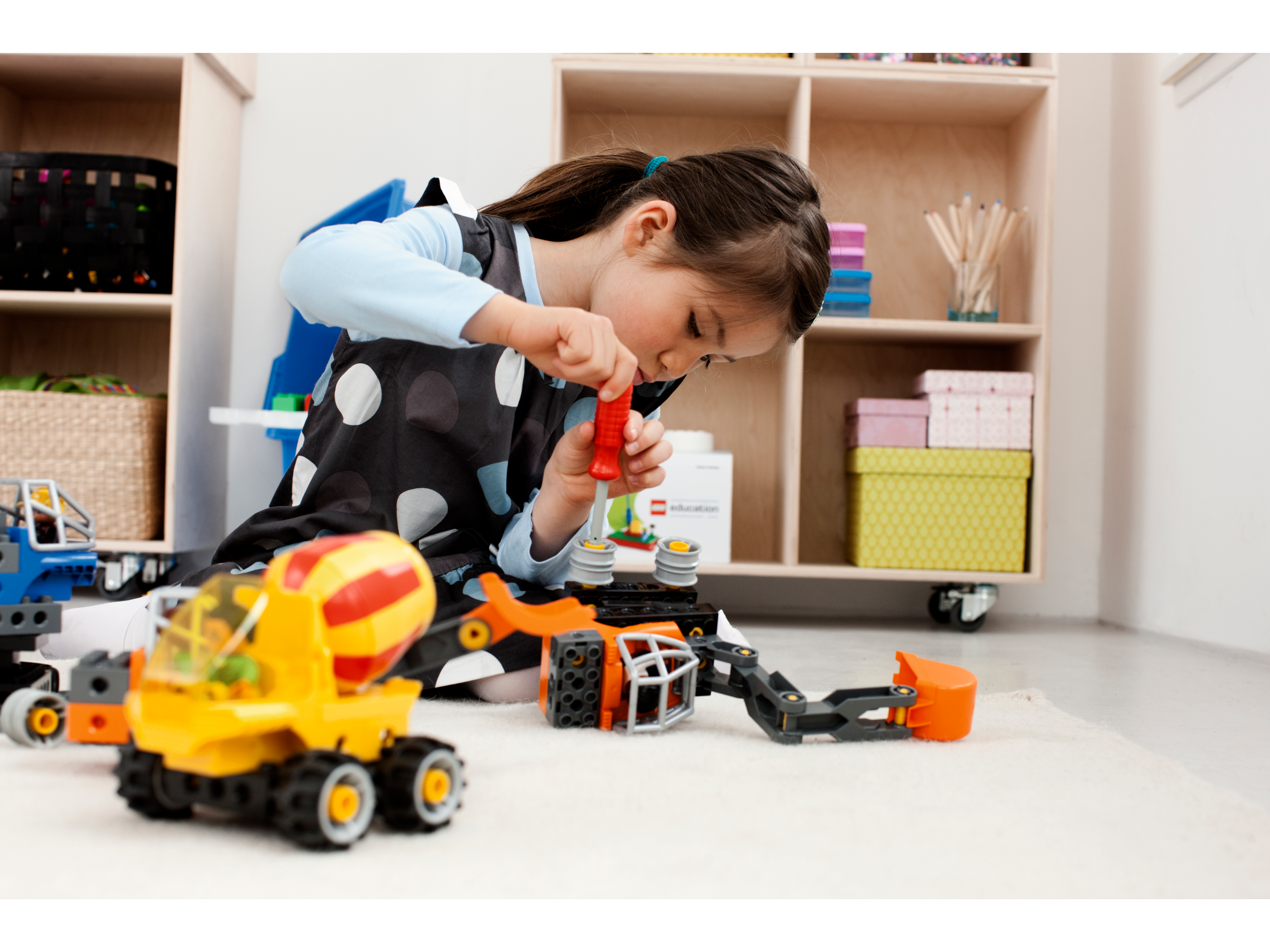 Preschool girl building with Tech Machines Set with Storage by LEGO® Education, developing her fine motor and problem-solving skills.