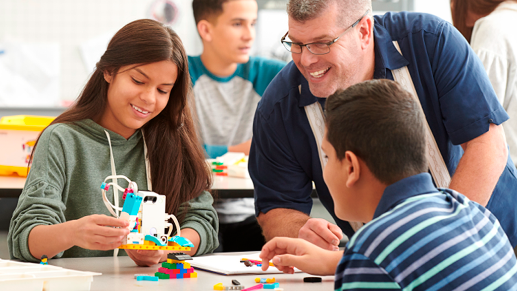 Middle school teacher helping two students build and code with LEGO® Education SPIKE™ Prime