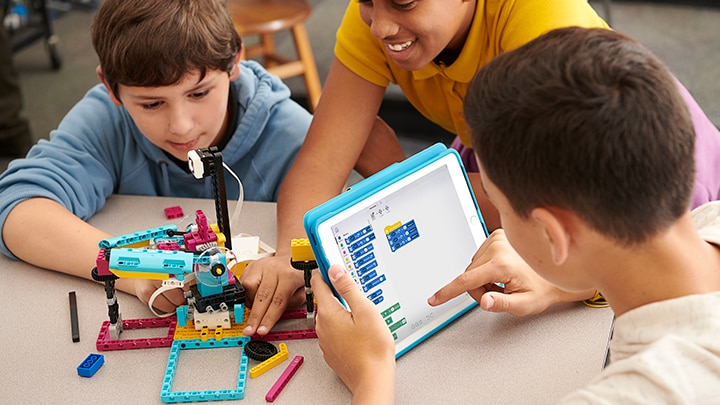 Three children coding and learning with the LEGO® Education SPIKE™ App